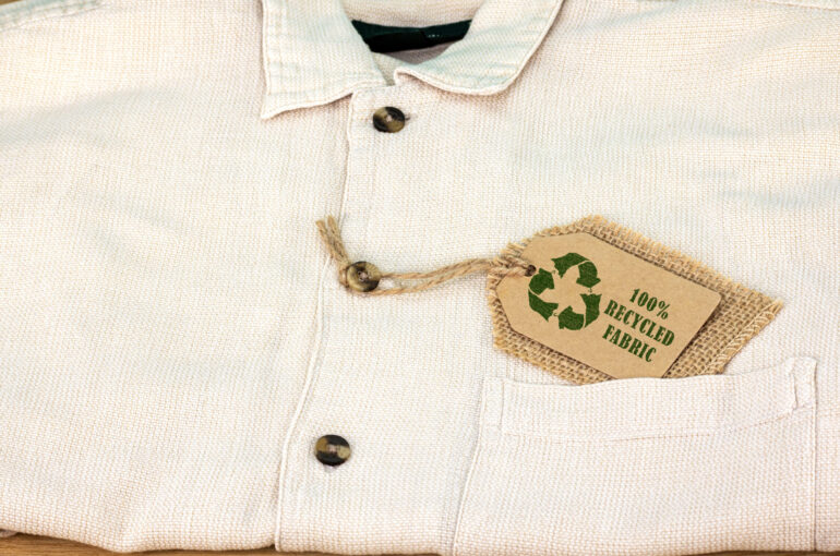 Recycle clothes icon on label with 100% Recycled fabric text. Sustainable fashion and ethical shopping conscious consumerism concept